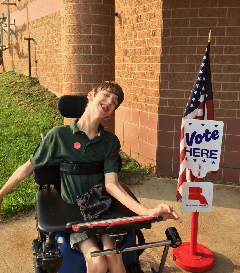 Justin with I voted sticker on next to Vote Here sign and US Flag