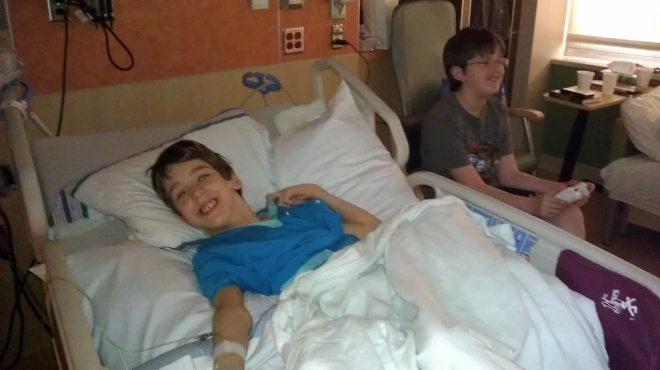 Justin laying in hospital bed, brother sitting in chair with game controller