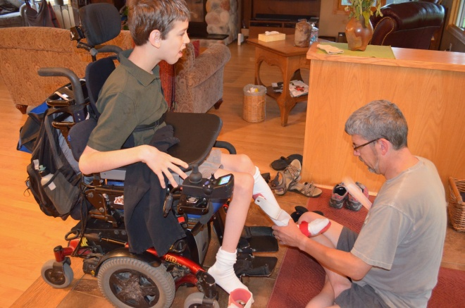 Justin in wheelchair, dad holding Justin's foot