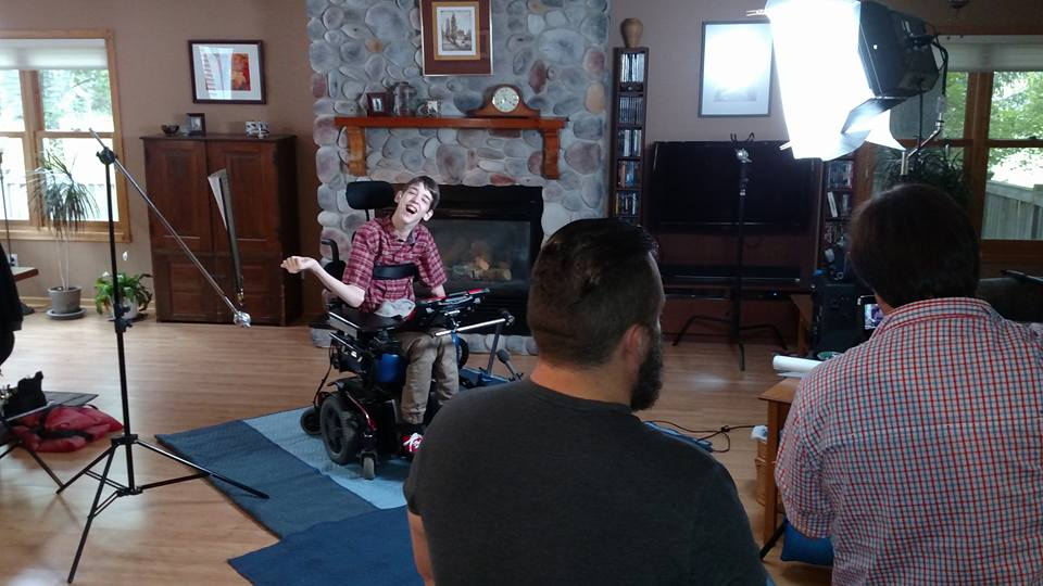 Justin in wheelchair with movie lights, 2 men looking at him with video camera