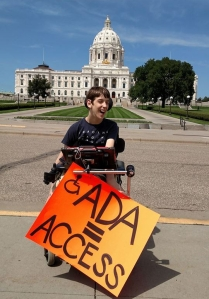 Justin in wheelchair holding ADA = Access sign in front of MN State Capitol
