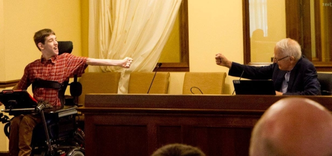 Justin reaching out to air-fist bump with Senator Durenberger