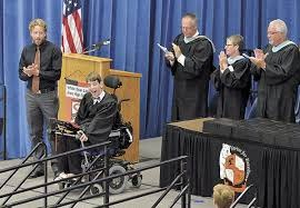 Justin in graduation gown near podium 4 adults standing and applauding