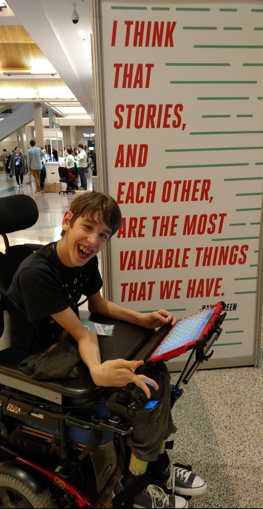 """Justin in wheelchair in front of poster that reads """"I think that stories, and each other, are the most valuable things that we have."""" Hank Green"""