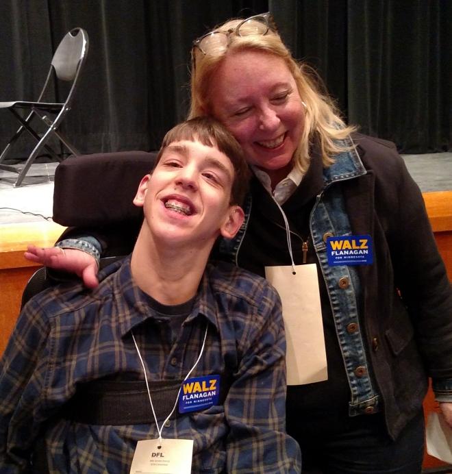 Woman hugging Justin, both wearing Walz Flanagan stickers