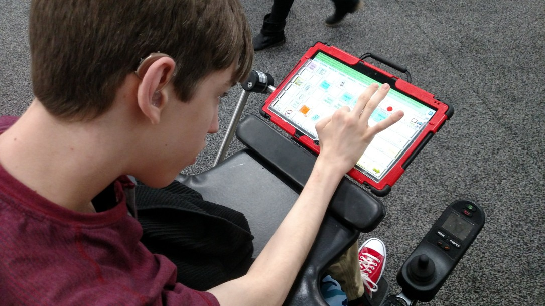 Justin in wheelchair typing on communication device