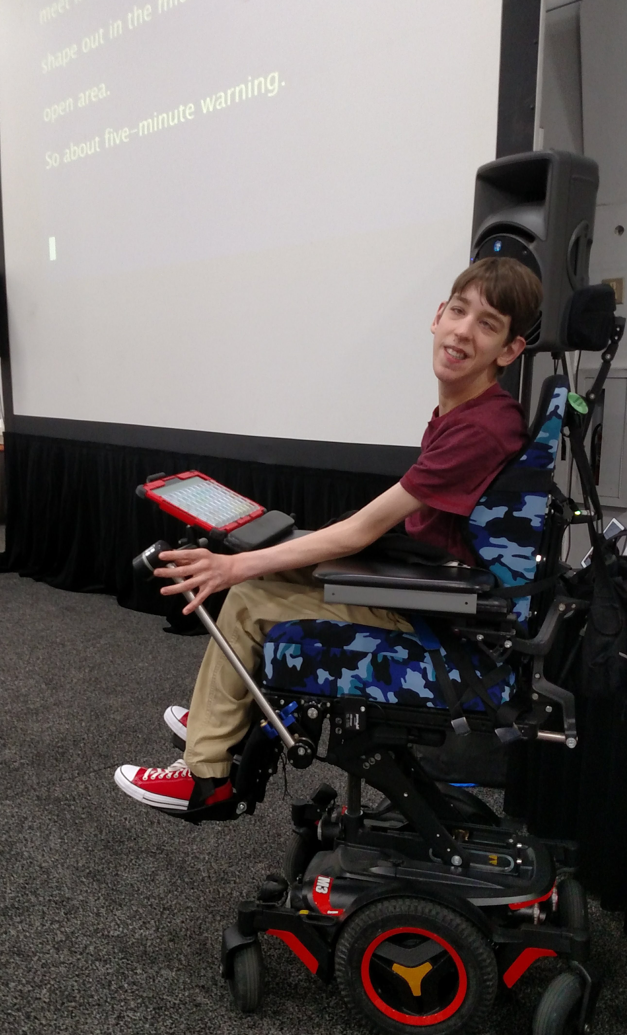 Justin in elevated wheelchair with screen displaying closed captions behind
