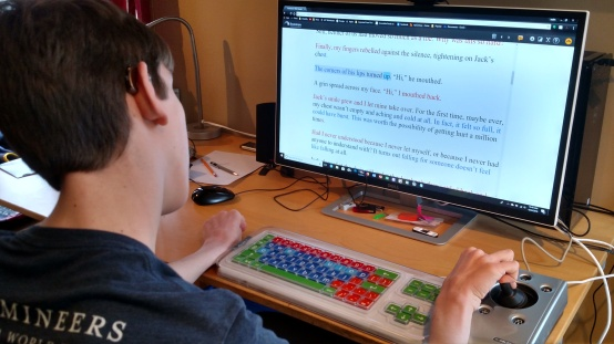 Justin looking at computer monitor with hand on joystick mouse