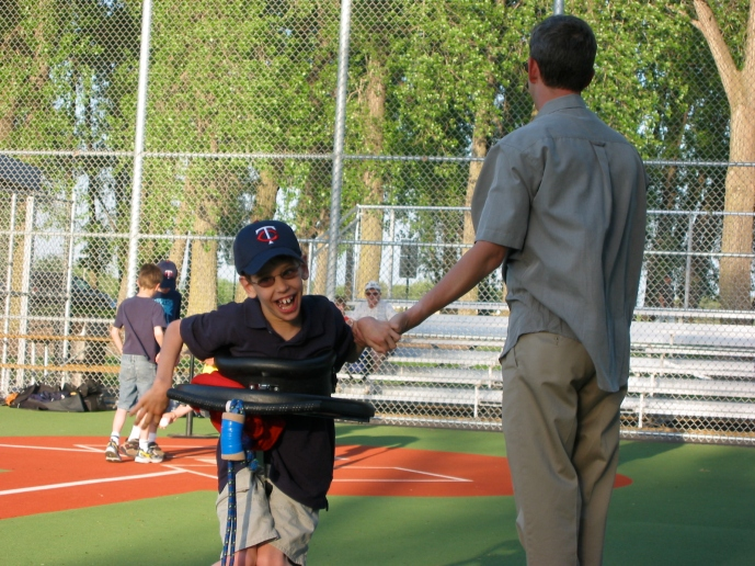 Justin in gait trainer giving high five to his dad on accessible baseball field