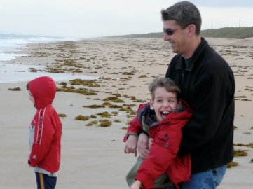 Dad holding Justin on beach by young boy
