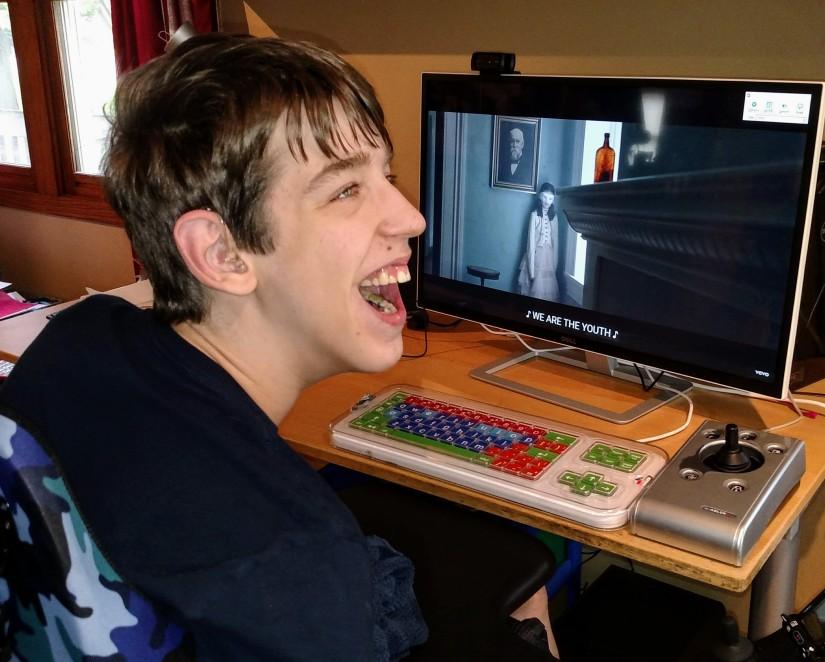 Justin smiling at computer monitor with captioned video