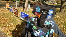 Back of Justin in his wheelchair covered with pins for MN DFL candidates looking at yard signs for DFL candidates