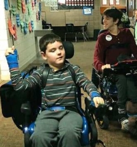 Boy and young man driving power wheelchairs in school hallway