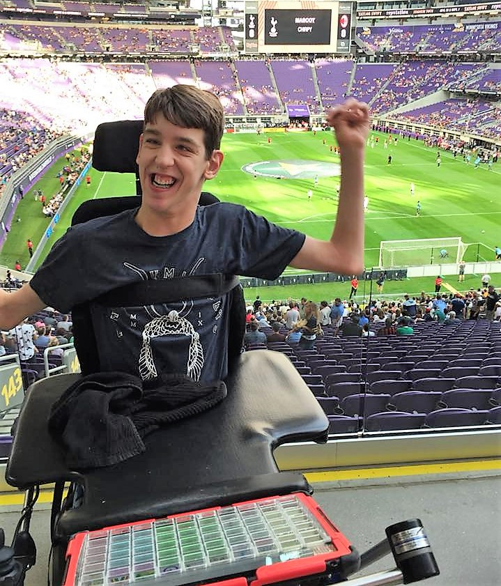 Smiling Justin sitting in wheelchair at soccer match in US Bank Stadium