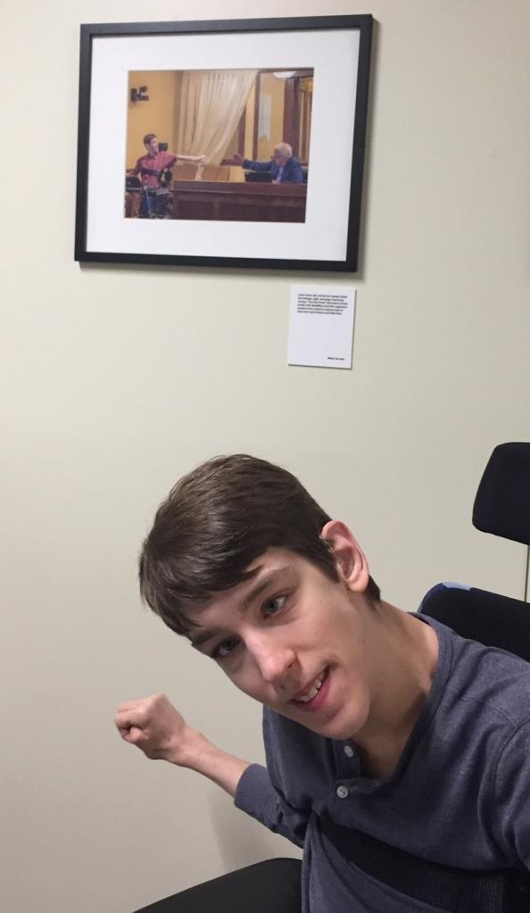 Justin in front of framed photo of him and Senator Durenberger