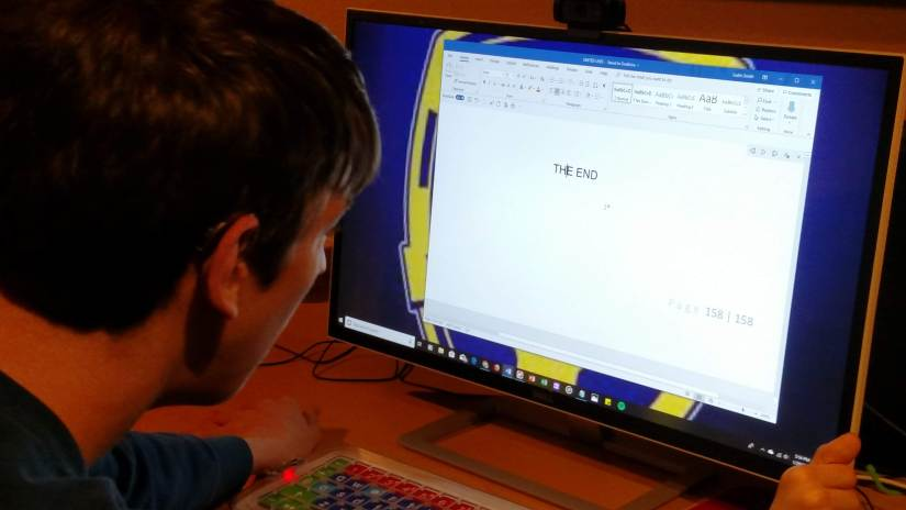 """Justin looking at word document that says """"the end"""" on computer monitor"""