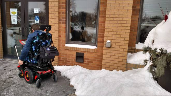 Justin in wheelchair outside door with pile of snow in front of accessible push button