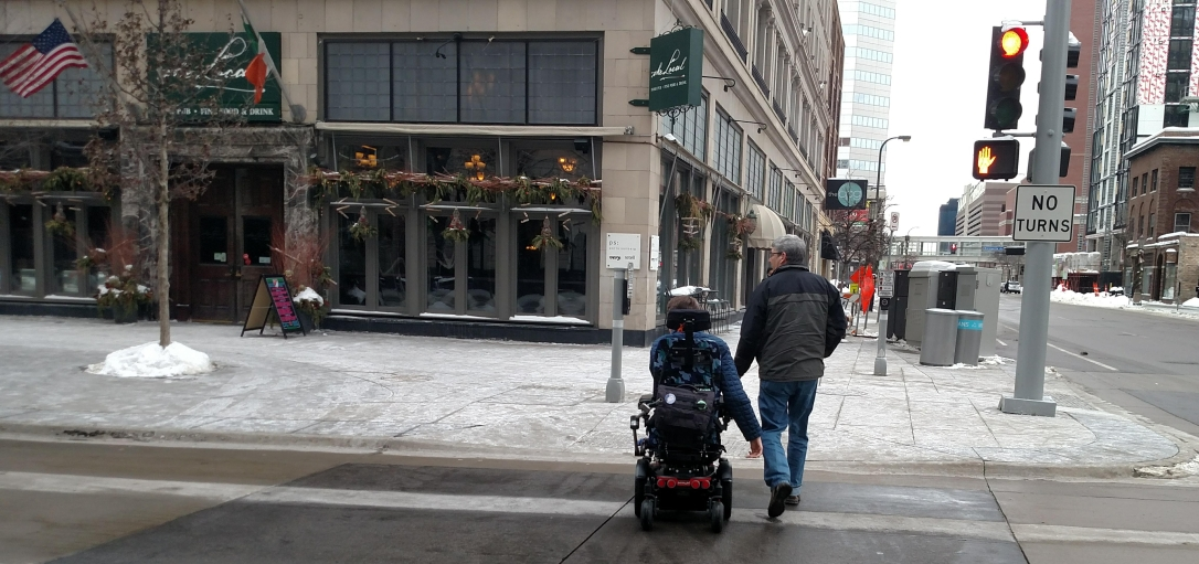 Justin in his wheelchair and dad crossing street