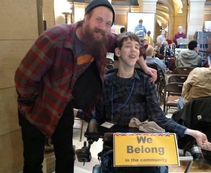 Man with arm around Justin, We belong in the community sign hanging on front of Justin's wheelchair