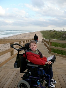 Justin as a boy at top of board walk ramp with sandy beach and ocean