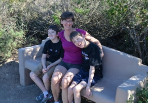 Justin, his mom and younger brother sitting on bench
