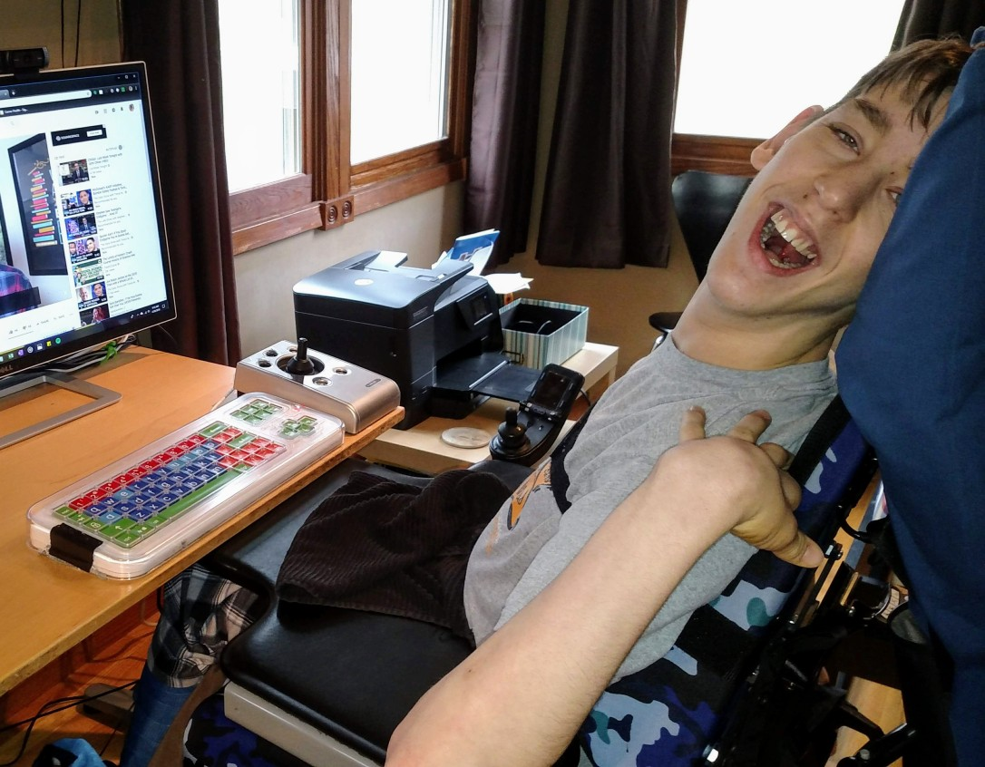 Justin sitting in wheelchair by computer