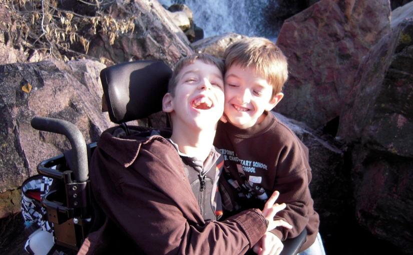 10 year old Justin getting hug from younger brother waterfall behind them