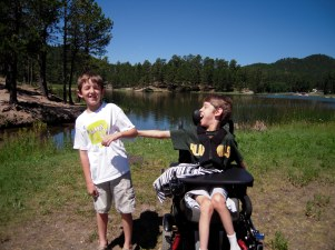 12 year old Justin with his brother with lake behind