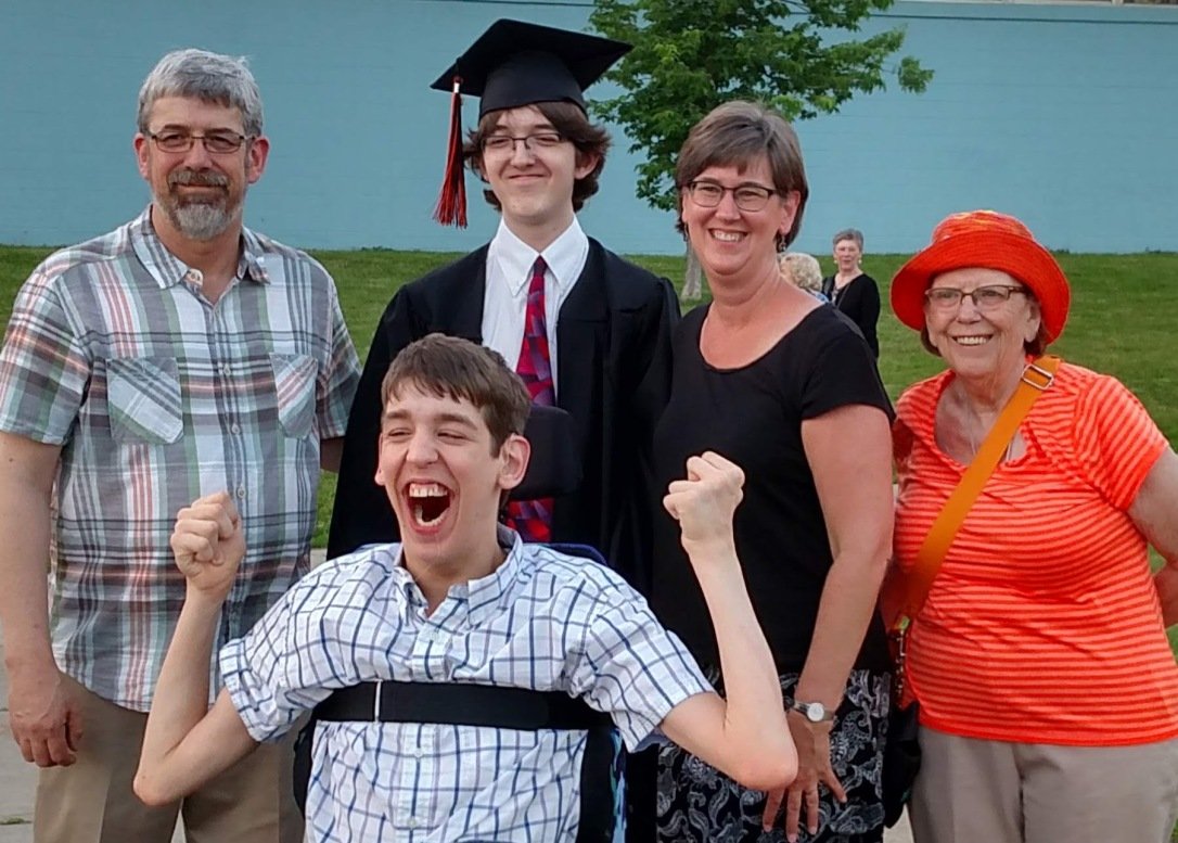 Justin, dad, graduate brother with cap and gown, mom and Grandma all smiling