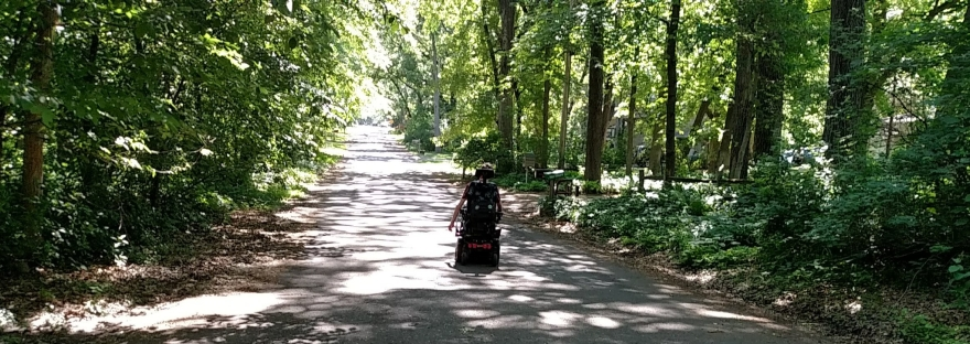 Wheelchair driving away on road