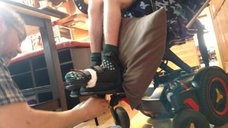 Dad working on wheelchair footrests with Justin's feet strapped in