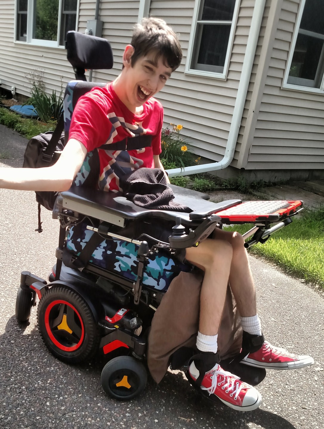 Justin smiling outside in his wheelchair