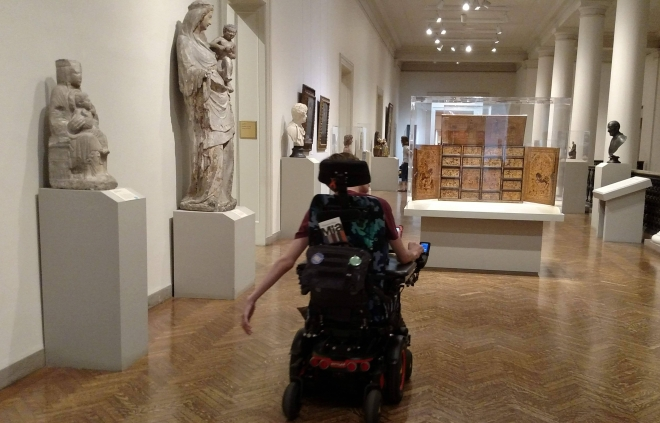 Justin driving wheelchair in art institute hallway with statues