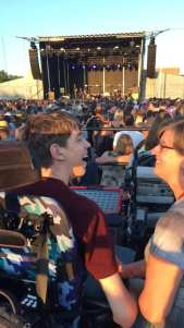 Justin and mom smiling at each other, crowd and stage in background