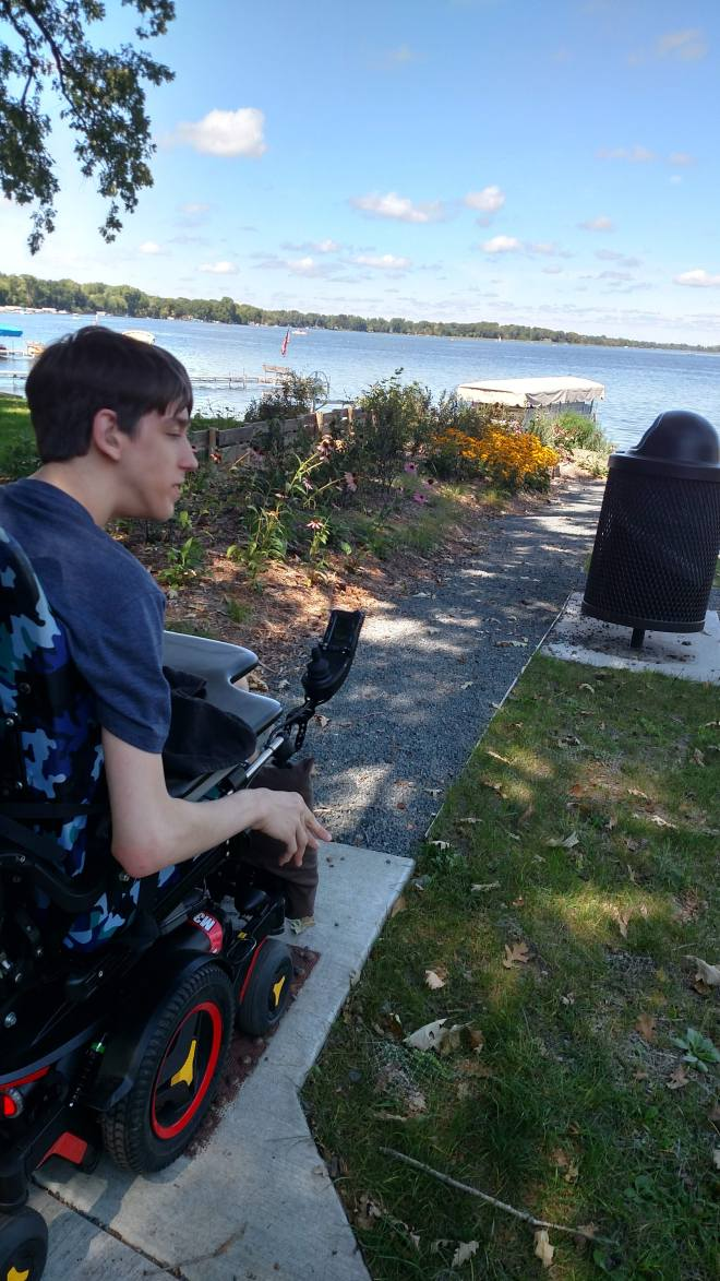 Justin in wheelchair on curb cut with path to lake ahead