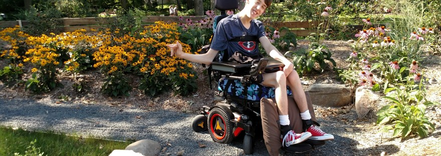 Justin smiling in wheelchair on path with flowers