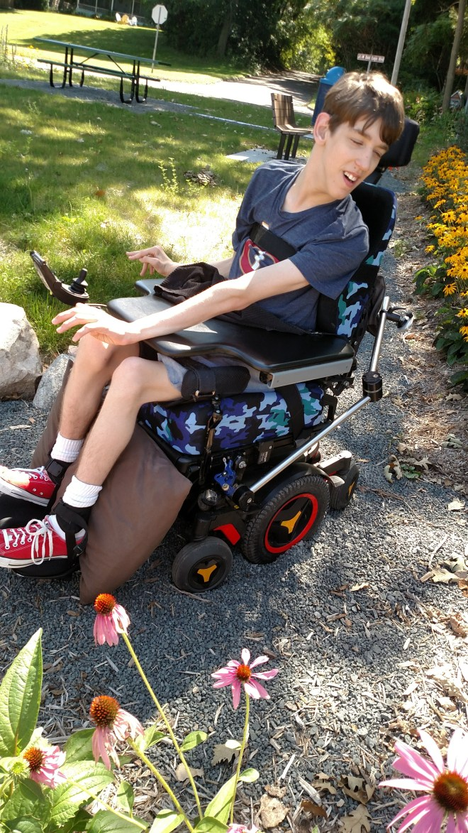 Justin in wheelchair with wheel sinking into rocky path