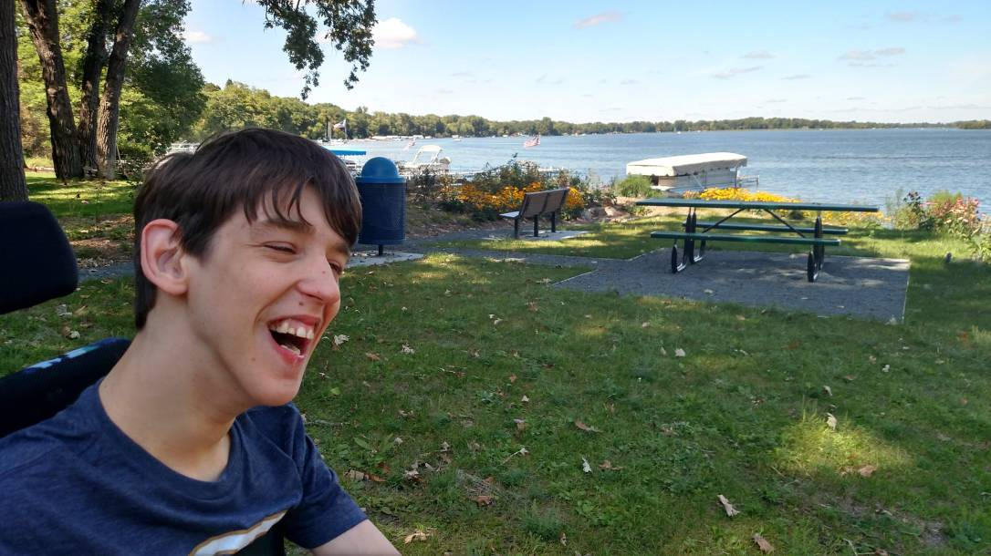 Justin smiling with park and lake behind