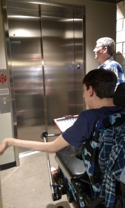 Justin and man waiting for elevator