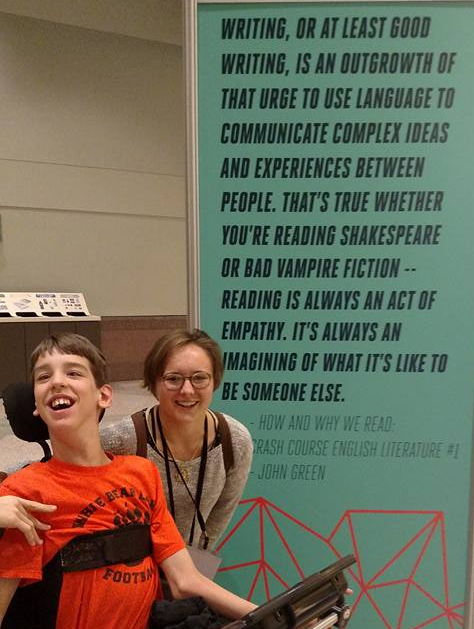 Justin and Annie in front of poster with John Green quote