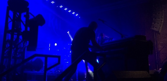 Delta Rae pianist on stage, blue concert lights