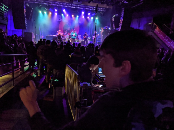 Justin looking across main floor crowd at 26 BATS! on First Avenue stage