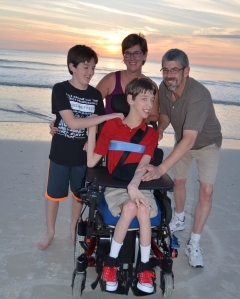Justin, younger brother, mom and dad smiling on sandy ocean beach
