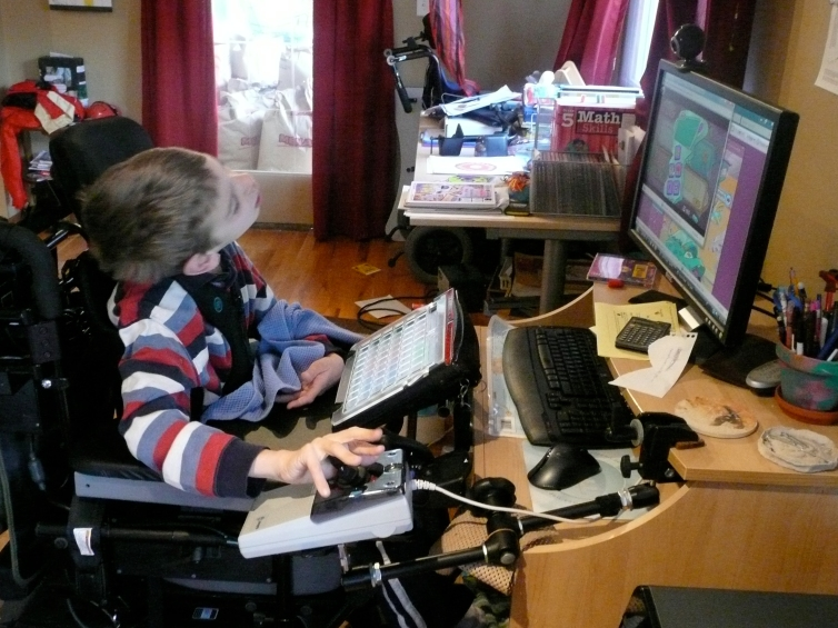 Justin in wheelchair with hand on joystick mouse looking at computer and communication device