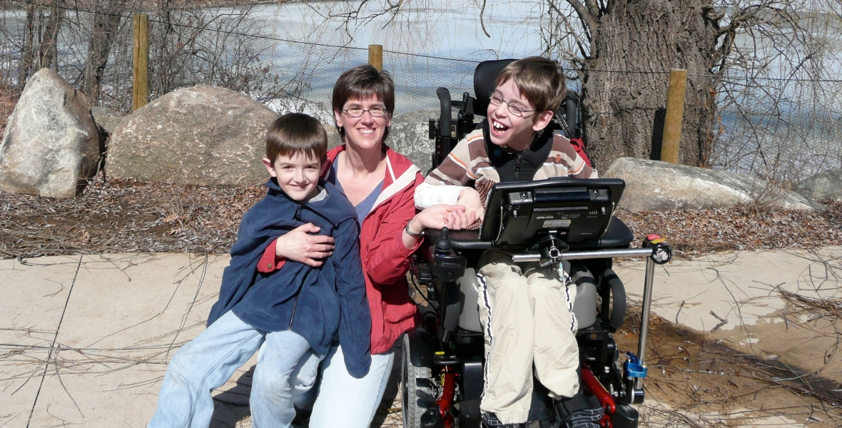 Young boy Justin in wheelchair, with mom and younger brother, lake