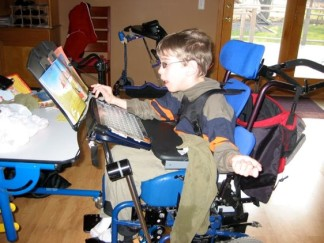 Justin in wheelchair, looking at book in adaptive book holder