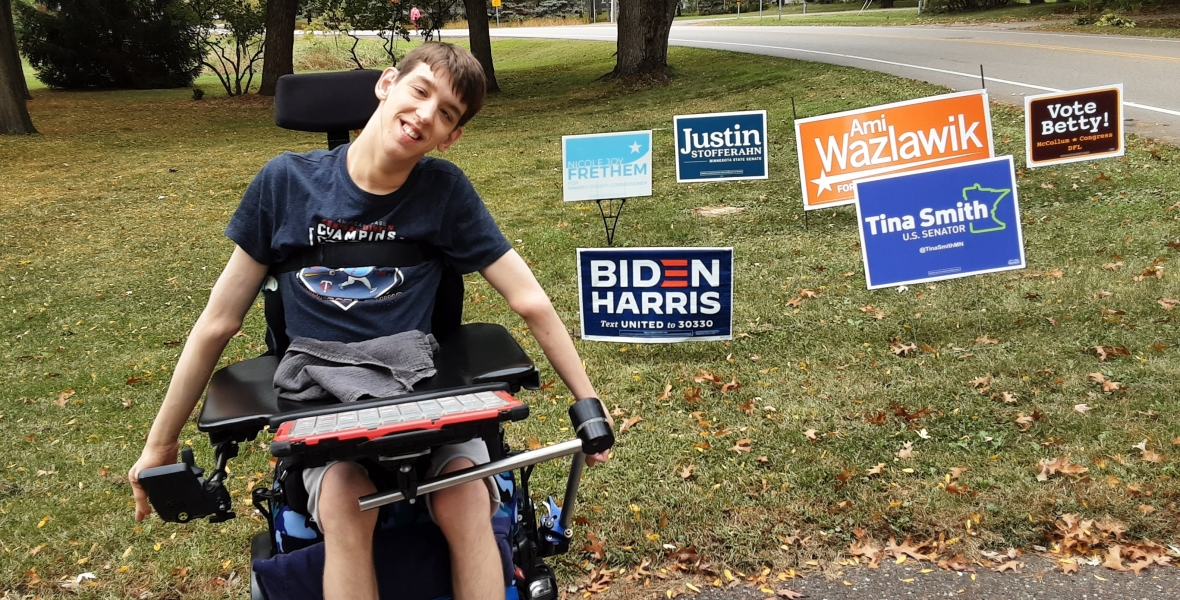 Justin smiling in front of Democrat candidate lawn signs