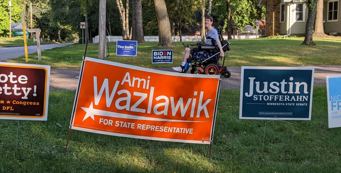 Justin smiling looking at political candidate signs in yard