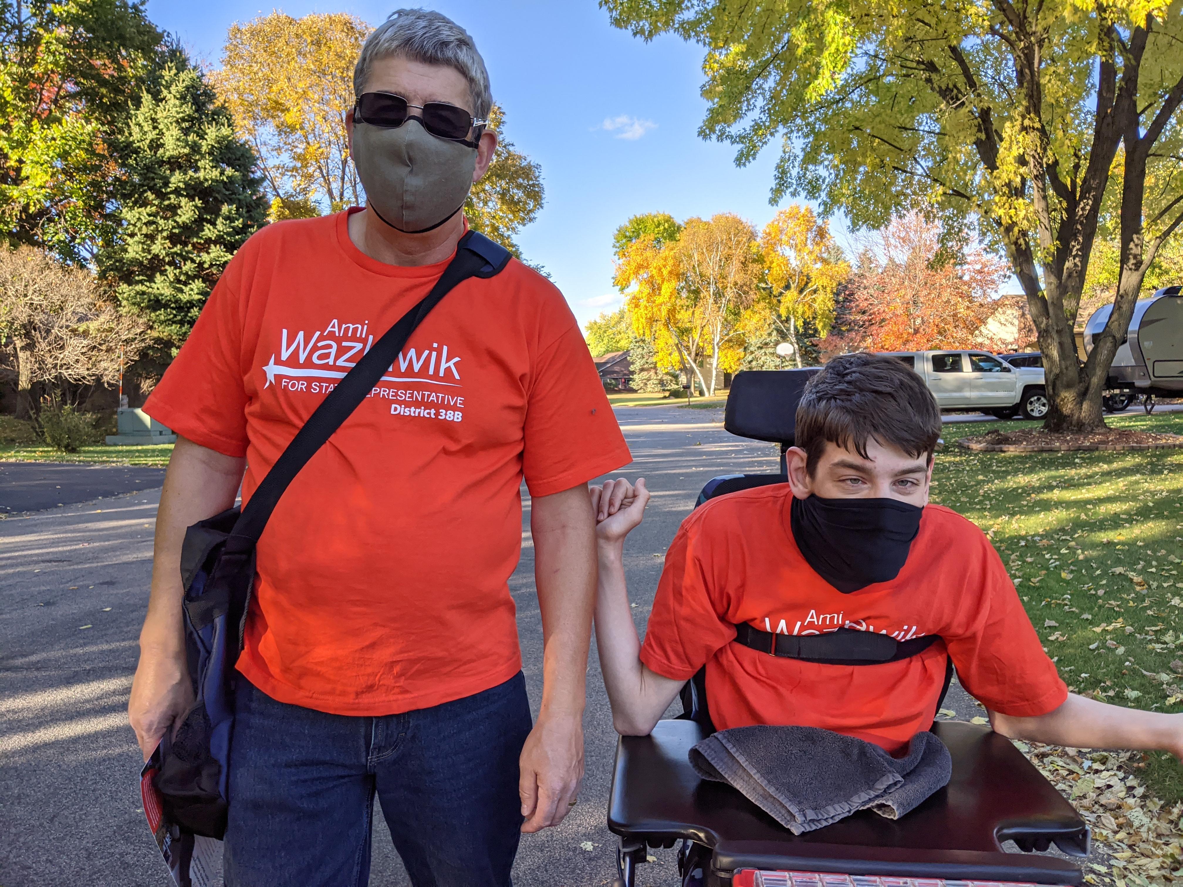 Justin and his dad wearing masks, wearing Ami Wazlawik t-shirts, on neighborhood street