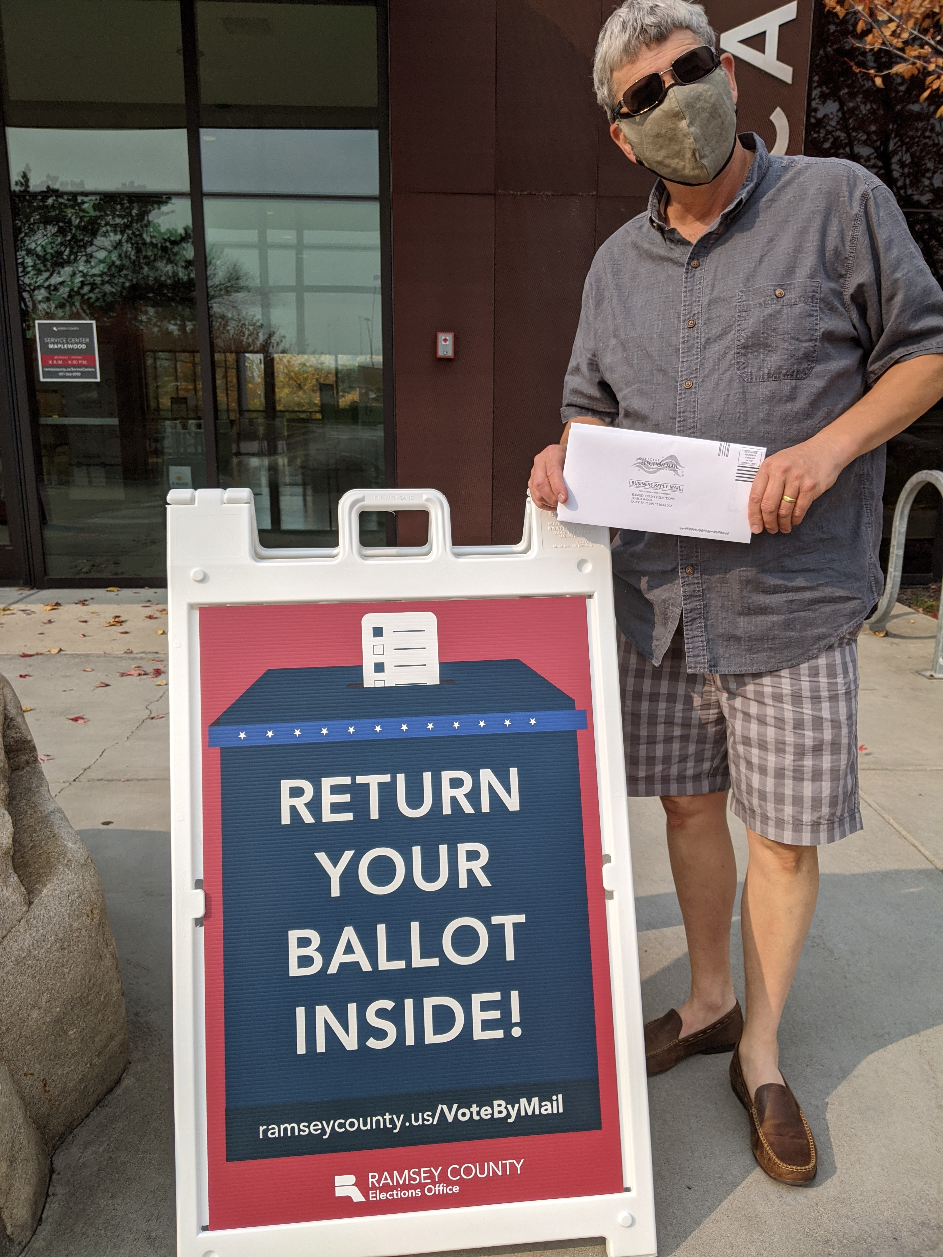 Man holding ballot in front of Ramsey County Return Your Ballot Inside sign